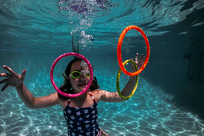 Smiling girl wearing swimming goggles while playing with colorful rings in pool - p1166m2067643 by Cavan Images