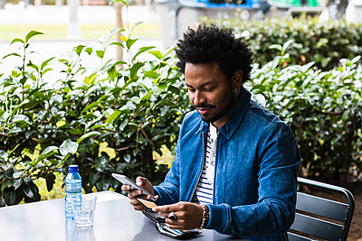 Man with afro hair using credit card and smart phone for paying at sidewalk cafe - p300m2244014 by NOVELLIMAGE