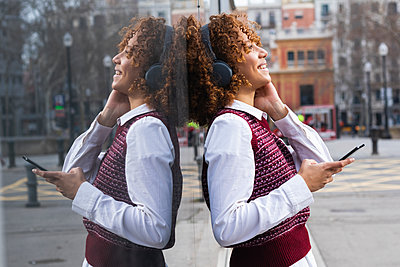 Cheerful woman wearing headphones standing with mobile phone against glass wall - p300m2267198 by NOVELLIMAGE