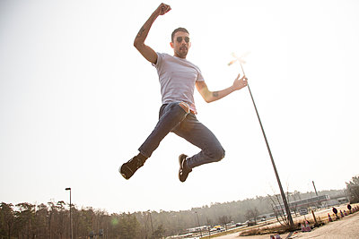 Young man jumping in the air, portrait - p975m2259768 by Hayden Verry