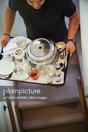 High angle view of man carrying breakfast tray up a staircase. - p1100m1490050 by Mint Images