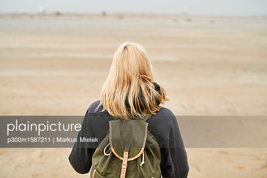 Back view of blond young woman with backpack on the beach - p300m1587211 von Markus Mielek