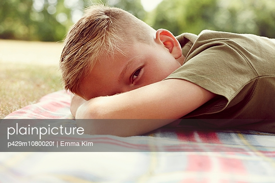 Surface level view of boy lying on picnic blanket, face obscured looking at camera - p429m1080020f by Emma Kim