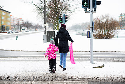Rear view of woman and daughter with sled walking on snow covered street - p1264m1122129f by Astrakan