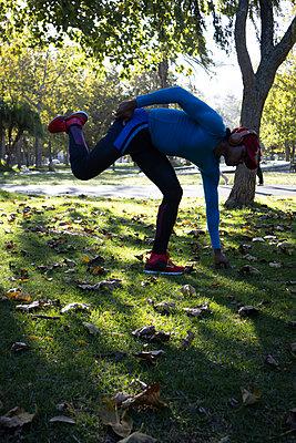 Dark-skinned man in sportswear warms up - p1640m2260992 by Holly & John
