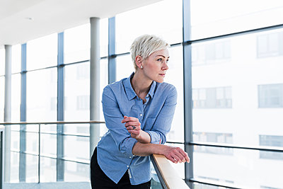 Woman in office building leaning on railing - p300m1581200 von Uwe Umstätter