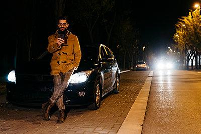 Spain, Igualada, man using cell phone outside the car at night - p300m2080596 von Josep Rovirosa