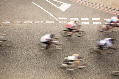 Overhead view of six cyclists speeding on urban road in racing cycle race - p429m1118416f by Seb Oliver
