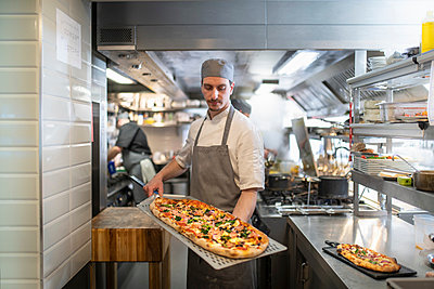 Chef in kitchen holding a Pinsa Romana, a Roman style pizza blend reducing sugar and saturated fat, containing rice and soy with less gluten - p429m2078557 by Monty Rakusen