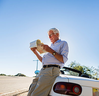Senior Caucasian man reading map by road - p555m1463835 by Marc Romanelli