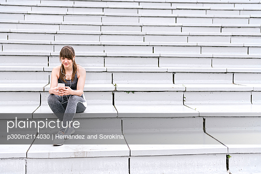 Young woman in sportswear sitting on concrete bleachers and listening music on a smartphone - p300m2114030 von Hernandez and Sorokina