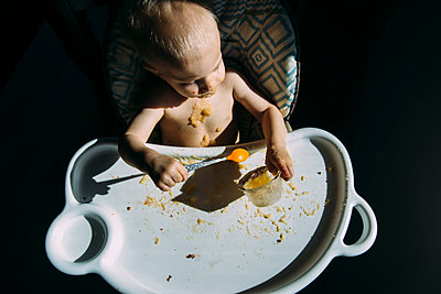 High angle view of shirtless baby boy eating food while sitting on high chair at home - p1166m1518973 by Cavan Images