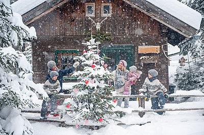 Austria, Altenmarkt-Zauchensee, family decorating Christmas tree at wooden house - p300m2041988 by Hans Huber