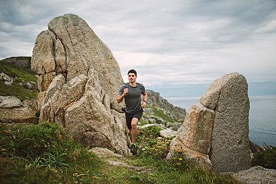 Trail runner in coastal landscape, Ferrol, Spain - p300m2132356 by Ramon Espelt