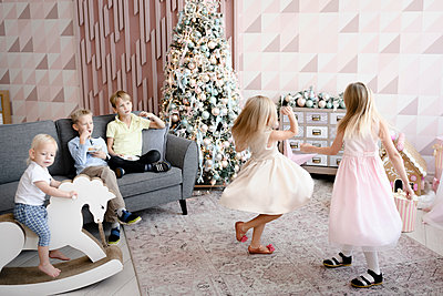 Two girls dancing in the living room while the boys watching them - p300m2139846 by Ekaterina Yakunina