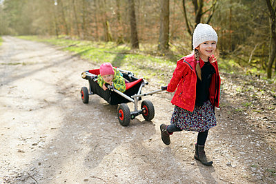 Portrait of little girl pulling trolley with her younger sister on forest track - p300m2197568 by Biederbick&Rumpf