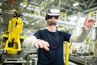 Man wearing VR glasses in modern factory - p300m2246018 by Westend61