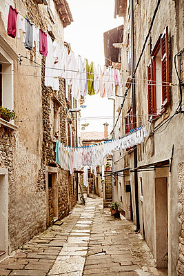 Laundry hanging above narrow street - p312m1187755 by Magnus Ragnvid