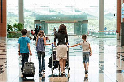 Family pushing luggage cart in airport, rear view - p623m659123f by Thierry Foulon