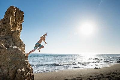 Boy jumping off rock, El Matador Beach, Malibu, USA - p924m1557693 by JLPH