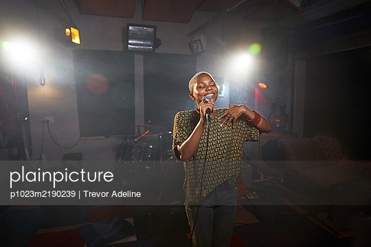 Female musician singing into microphone in recording studio - p1023m2190239 by Trevor Adeline
