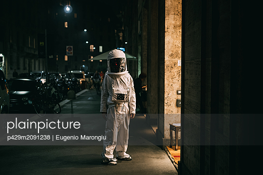 Astronaut walking on pavement at night - p429m2091238 by Eugenio Marongiu