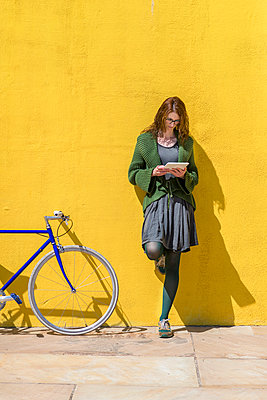 Businesswoman using tablet computer while standing by bicycle on sidewalk against yellow wall during sunny day - p1166m2060570 by Cavan Social