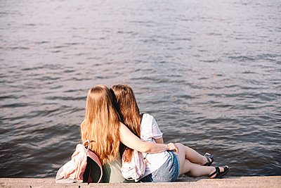 Back view of lesbian couple embracing while sitting on steps by river - p1166m2212425 by Cavan Images