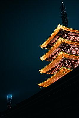 Pagode eines japanischen Tempels bei Nacht mit modernem Gebäude im Hintergrund - p1180m1446105 von chillagano