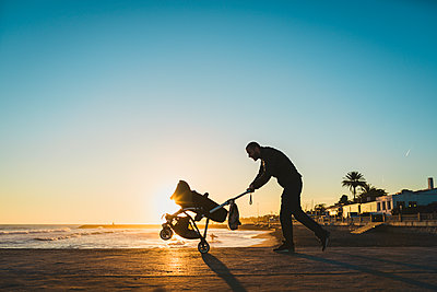 Man walking with a stroller on the seashore at sunset - p300m1204848 by Gemma Ferrando