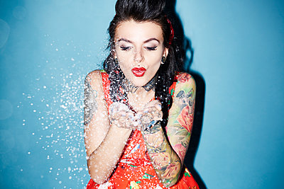 Portrait of tattooed woman blowing artificial snow - p300m1567638 by gpointstudio
