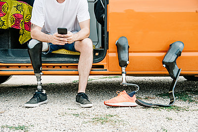 Young man with leg prosthesis sitting in camper van using cell phone - p300m2139712 by Jesús Martinez