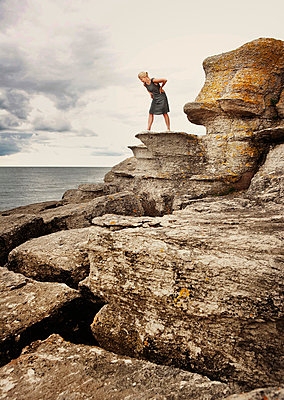 Woman standing on rock on coast - p312m714749 by Bruno Ehrs
