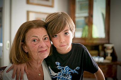 Caucasian grandmother and grandson hugging - p555m1306032 by Alberto Guglielmi