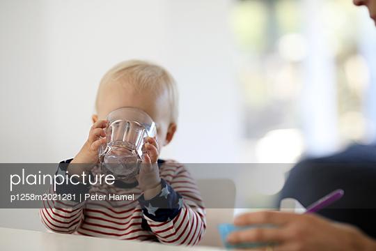 Kleinkind trinkt aus großem Glas - p1258m2021281 von Peter Hamel