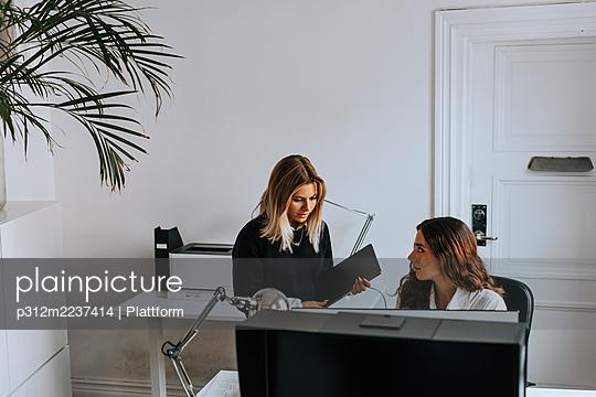 Female coworkers talking in office - p312m2237414 by Plattform