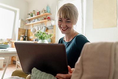 Portrait of happy woman sitting in the kitchen using laptop - p300m2140875 by Kniel Synnatzschke