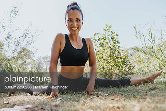Sportswoman smiling while doing splits at park - p300m2256268 by Mareen Fischinger