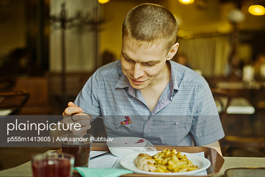 Caucasian man eating lunch at table - p555m1413605 by Aleksander Rubtsov