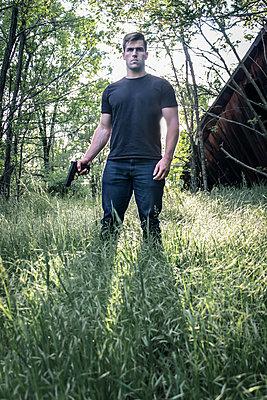 Mann mit Pistole in einer Wiese - p1019m1424620 von Stephen Carroll