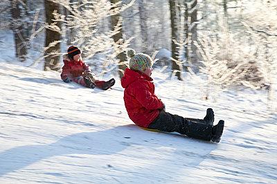 Sweden, Two children sliding down slope in winter - p1687m2284305 by Katja Kircher