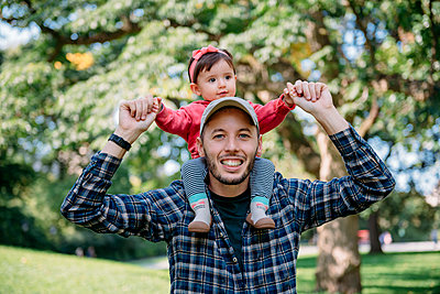 USA, New York, Father with baby girl on his shoulders walking through Central Park - p300m2012539 by Gemma Ferrando