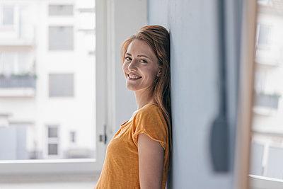 Happy woman leaning on wall - p300m2023977 von Joseffson
