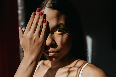 Young woman covering eyes with hand - p300m2265545 by MORNINGVIEW AGENCY
