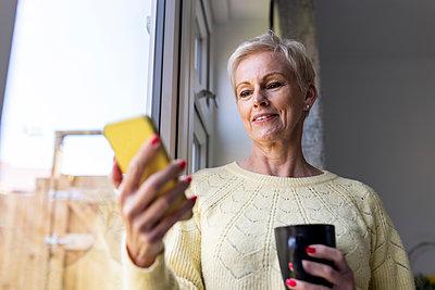 Woman using smart phone at home - p300m2293936 by William Perugini