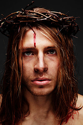 Young man as Jesus wearing crown of thorns, studio shot - p528m713773 by Magnus Ragnvid