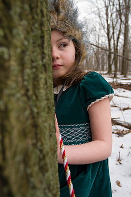 Little girl hiding behind a tree - p5830091 by Kristina Williamson