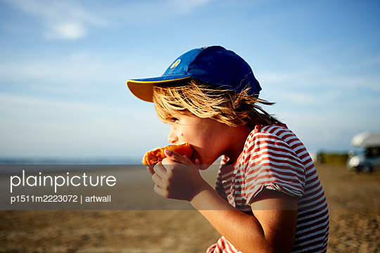 Little boy with peaked cap eating on the beach - p1511m2223072 by artwall