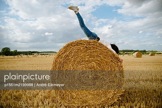 Woman lying on bale of straw - p1551m2199988 by André Eikmeyer