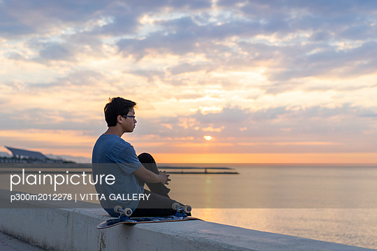 Young Chinese man with skateboard sitting on wall at the beach - p300m2012278 von VITTA GALLERY